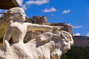 Model of Crazy Horse sculpture with the uncompleted sculpture on Thunder Mountain in background -photo from